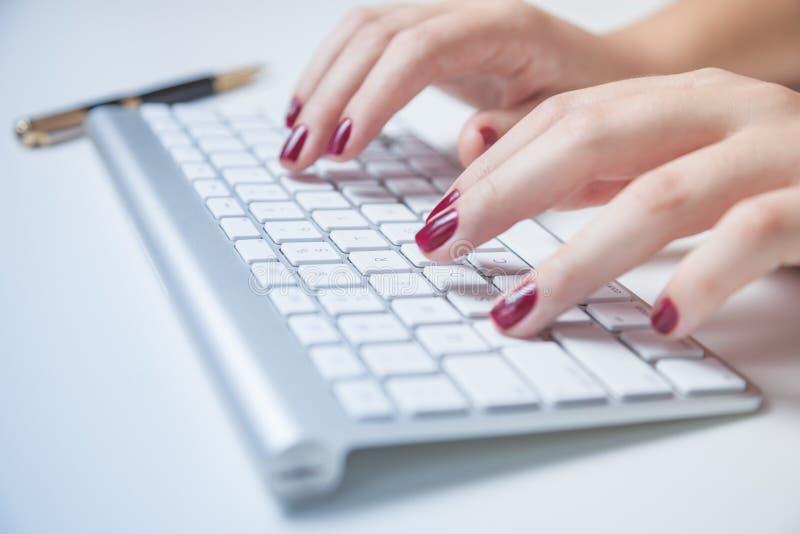 Plan rapproché de la main de femme d'affaires dactylographiant sur le clavier images stock