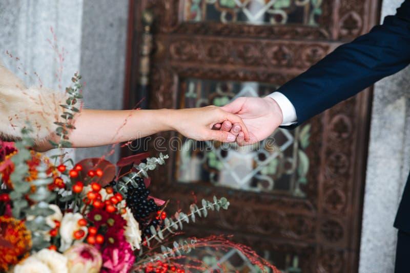 Plan rapproché de la main du marié tenant l'offre de wirst de la main de la jeune mariée photos stock