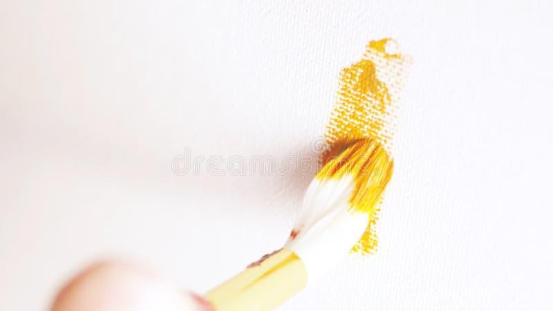 Plan rapproché de la main du peintre avec le grand dessin de brosse blanc la ligne par la peinture d'huile d'oranges sur la toile images stock