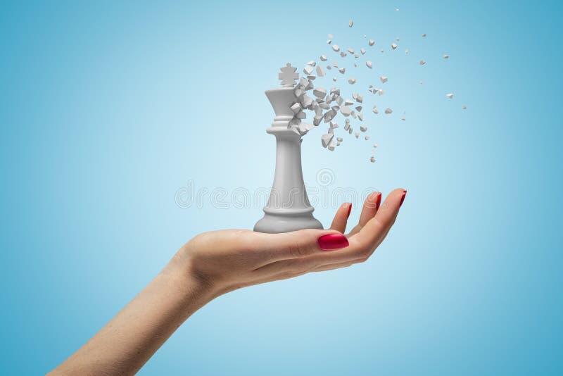 Plan rapproché de la main de la femme faisant face et tenant le grand roi blanc d'échecs qui a commencé à se dissoudre dans des m photographie stock libre de droits