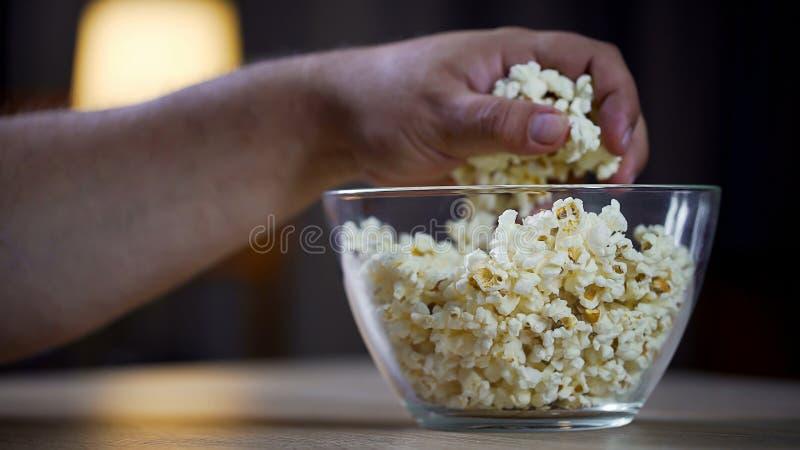 Plan rapproché de la main masculine prenant le maïs éclaté de la cuvette sur la table, intoxiqué malsain de nourriture photo stock