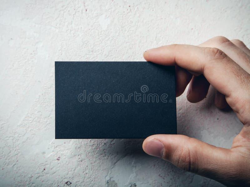 Plan rapproché de la main masculine tenant la carte de visite professionnelle de visite noire image stock