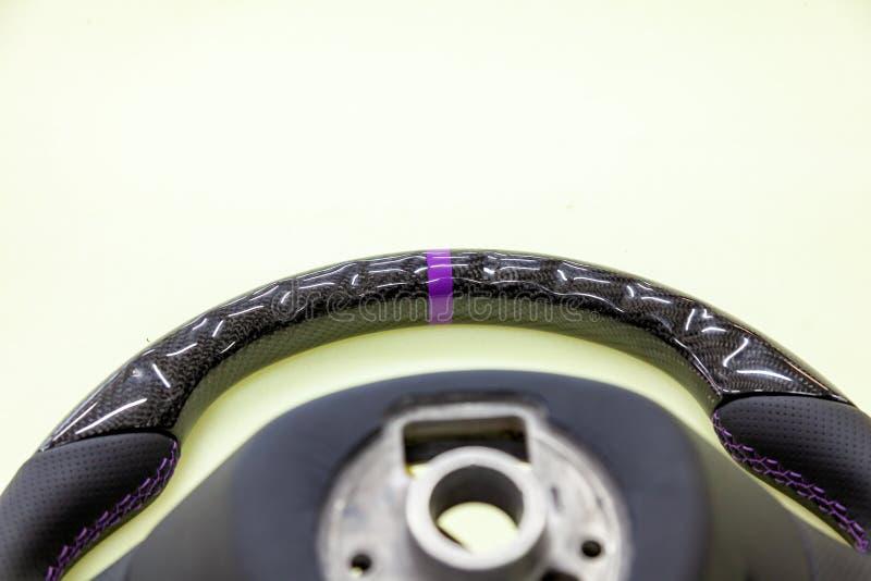 Plan rapproché de la partie supérieure d'un volant exotique de concepteur fait en fibre noire de carbone avec le cuir perforé piq photos stock