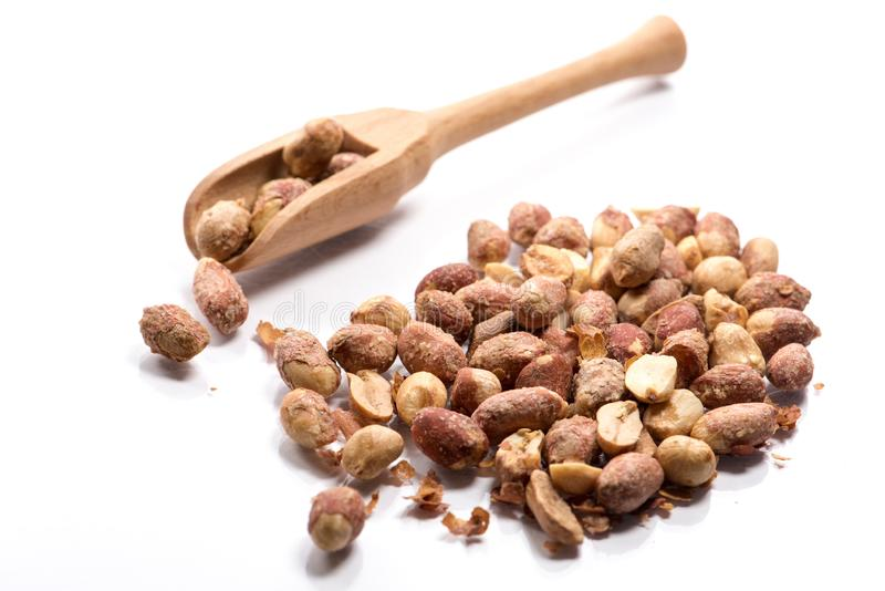 Plan rapproché de la pile des arachides dessus rôties et salées dans une cuillère en bois photographie stock libre de droits