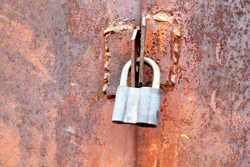 Plan rapproché de la serrure de porte sur le métal rouillé souillé images libres de droits