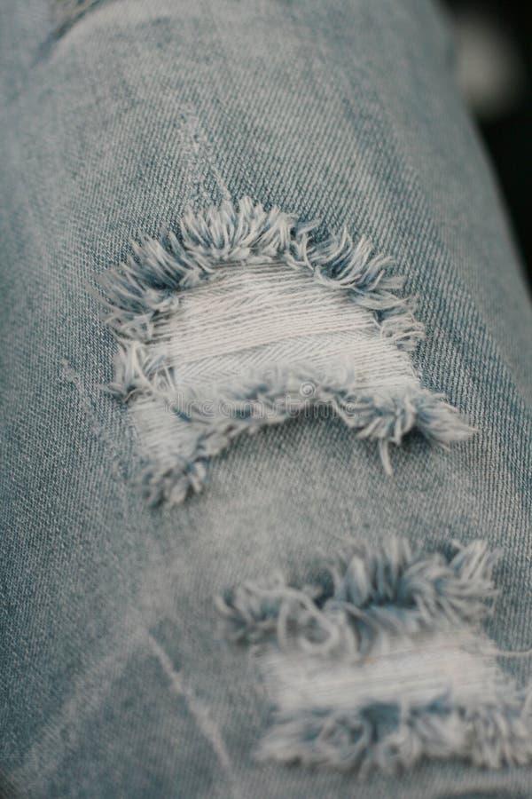 Plan rapproché de larme dans de vieux utilisés jeans photos stock