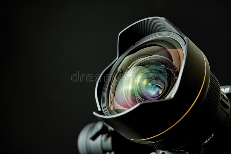 Plan rapproché de lentille grande-angulaire dans une caméra de DSL, avec l'éclairage discret et un fond noir photographie stock libre de droits