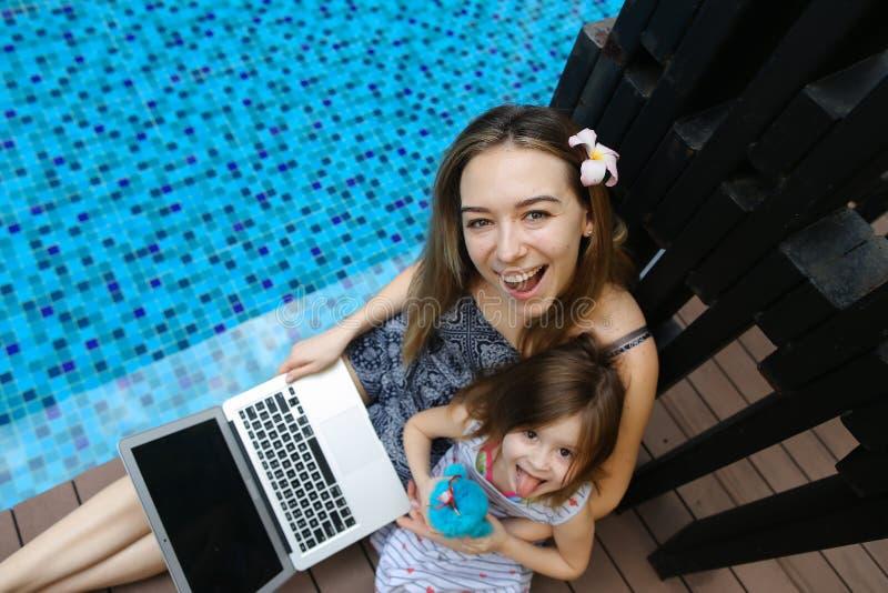 Plan rapproché de mère, de fille et d'ordinateur portable femelles sur le fond de la piscine images libres de droits