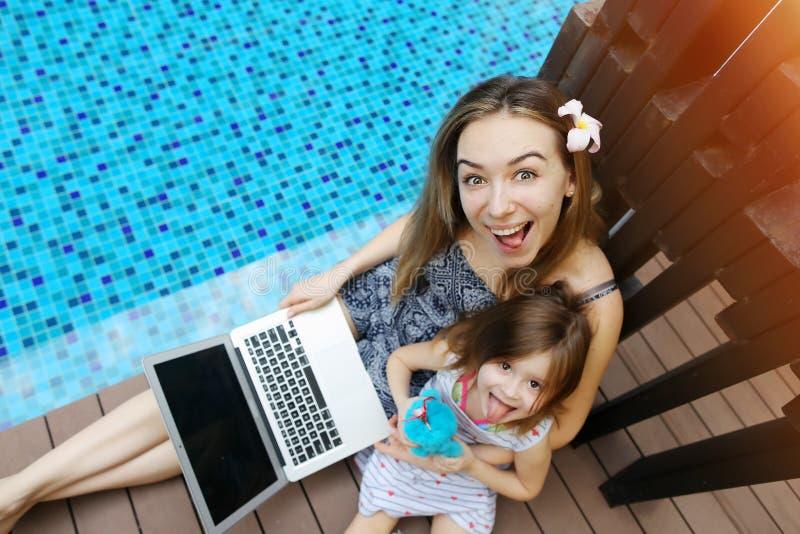 Plan rapproché de mère, de fille et d'ordinateur portable femelles sur le fond de la piscine photo libre de droits