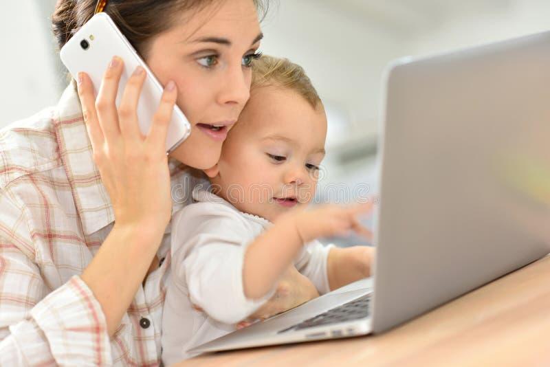 Plan rapproché de mère occupée et de son bébé sur l'ordinateur portable photographie stock libre de droits