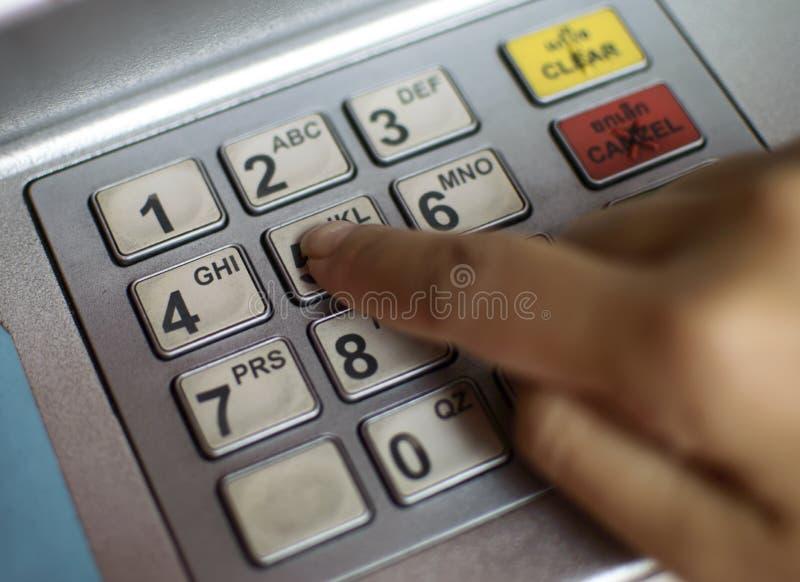 Plan rapproché de main écrivant le code de PIN/pass sur le clavier numérique de machine d'ATM/bank images libres de droits