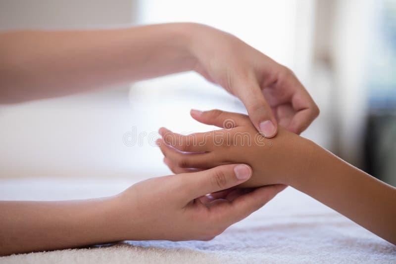 Plan rapproché de main de examen de thérapeute féminin sur la serviette blanche photos libres de droits