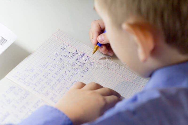 Plan rapproché de main de garçon avec le crayon écrivant des mots anglais à la main sur le papier blanc traditionnel de bloc-note photos libres de droits