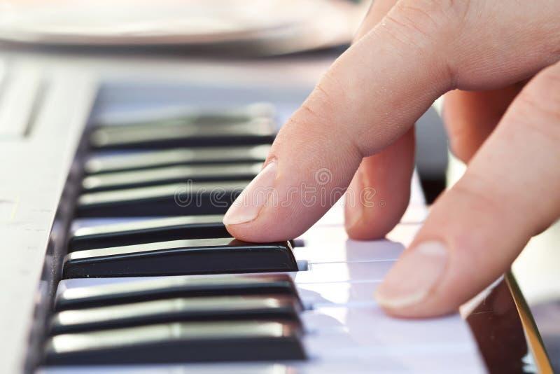 Plan rapproché de main jouant le piano photographie stock libre de droits