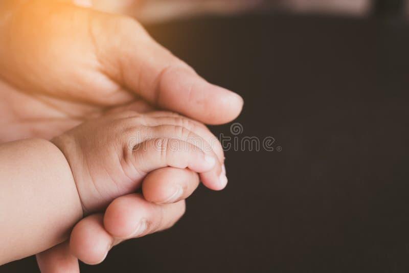 Plan rapproché de main nouveau-née du ` s de bébé dans la main du ` s de mère photographie stock libre de droits