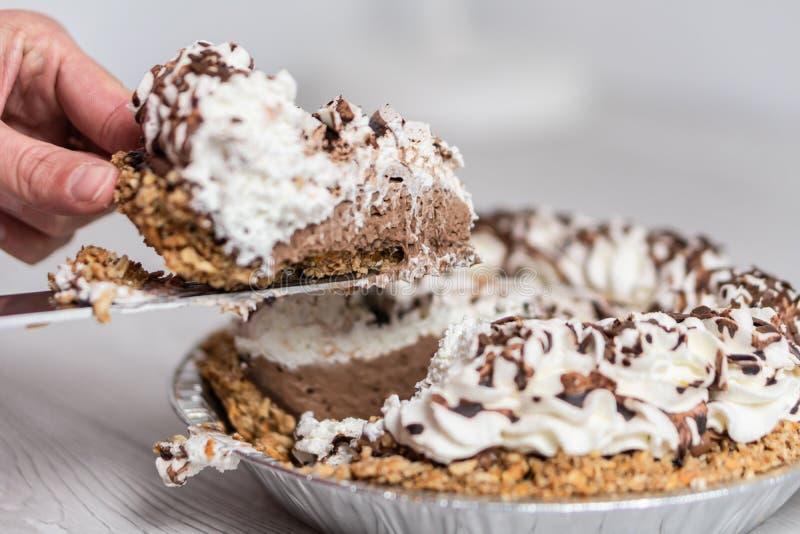 Plan rapproché de main prenant un morceau de tarte crème délicieux prêt au serveur, à l'écrimage de crème et de chocolat image libre de droits
