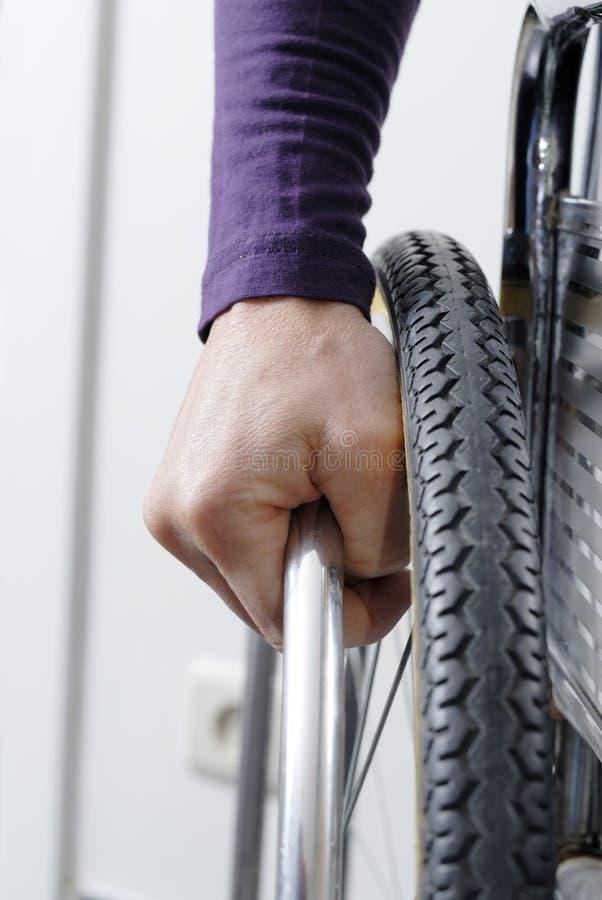 Plan rapproché de main sur la roue du fauteuil roulant photographie stock