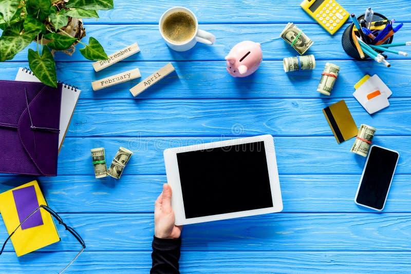 Plan rapproché de main tenant le comprimé numérique sur la table en bois bleue avec l'argent et la papeterie images libres de droits