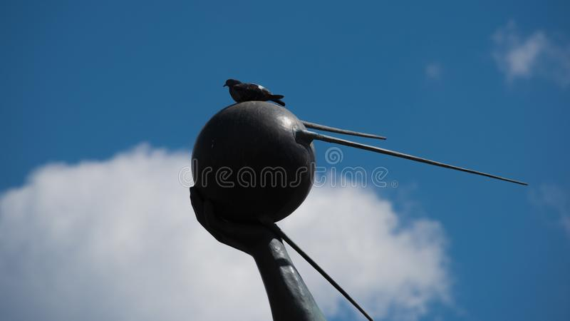 Plan rapproch? de main tenant le premier satellite de terre artificiel avec la colombe se reposant l?-dessus photographie stock