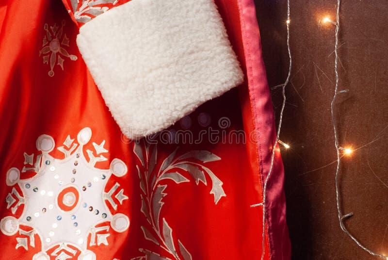 Plan rapproché de manteau de fourrure de Santa Claus, de vêtements de Santa et de guirlande rouges, fond de nouvelle année, images stock
