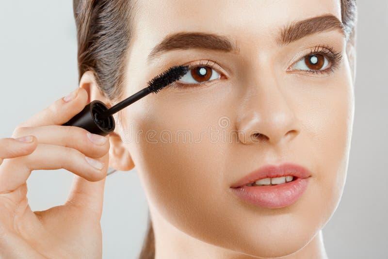 Plan rapproché de mascara d'un beau visage de la jeune femme A avec un maquillage de beauté, peau molle fraîche appliquant le mas photographie stock libre de droits