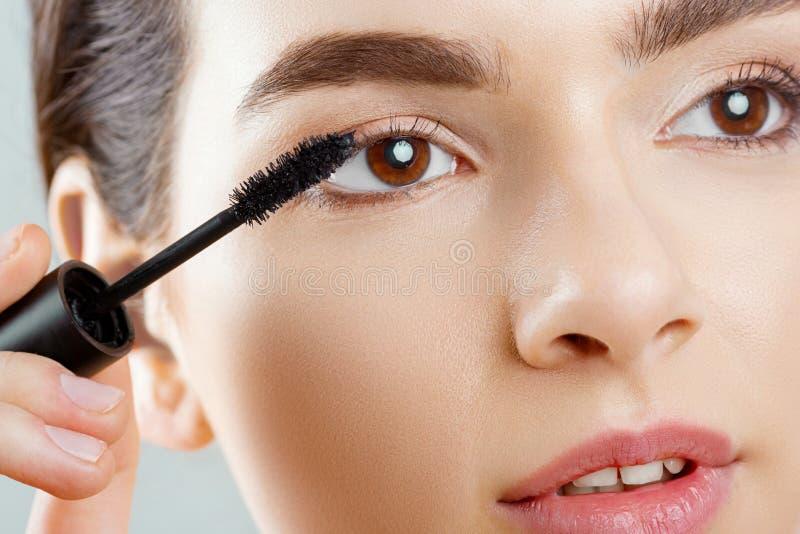 Plan rapproché de mascara d'un beau visage de la jeune femme A avec un maquillage de beauté, peau molle fraîche appliquant le mas photo libre de droits