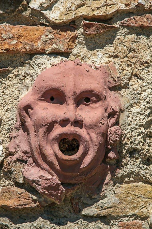 Plan rapproché de masque d'argile fixé au mur en ` Elsa de Colle di Val d images libres de droits