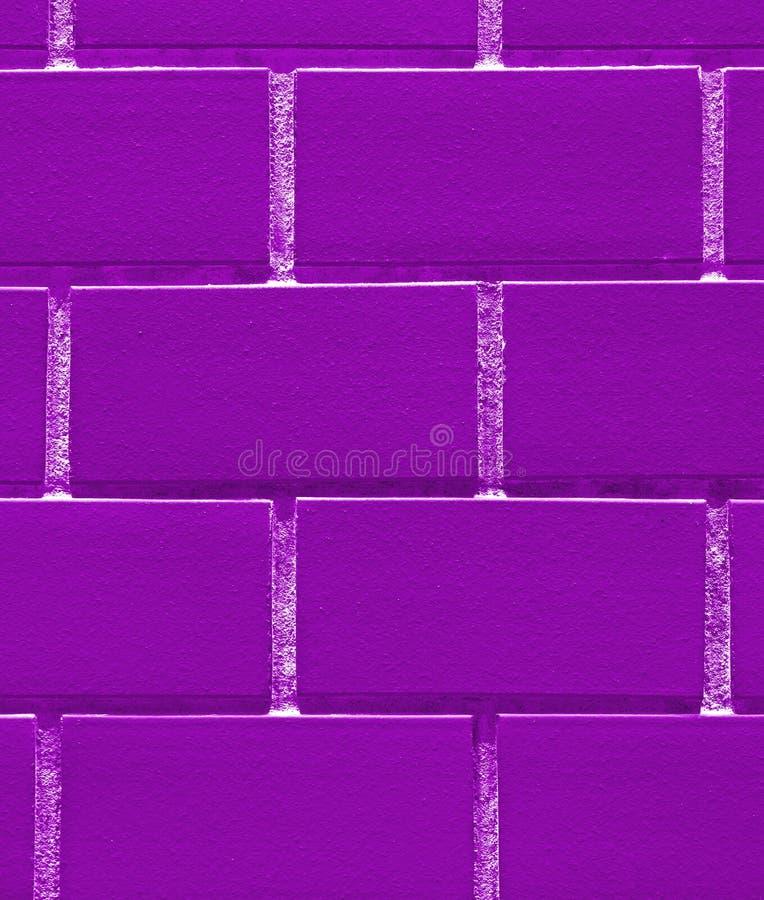 Plan rapproché de mur de briques dans la couleur pourpre vive, pour le fond image libre de droits