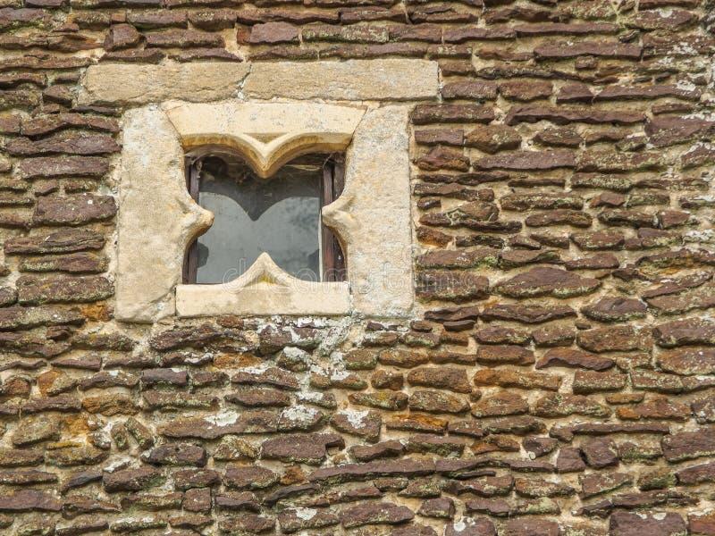 Plan rapproché de mur en pierre antique avec une fenêtre carrée intéressante images stock
