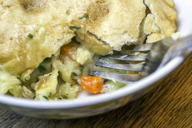 Plan rapproché de pâté en croûte savoureux de poulet avec la fourchette dans la croûte image stock