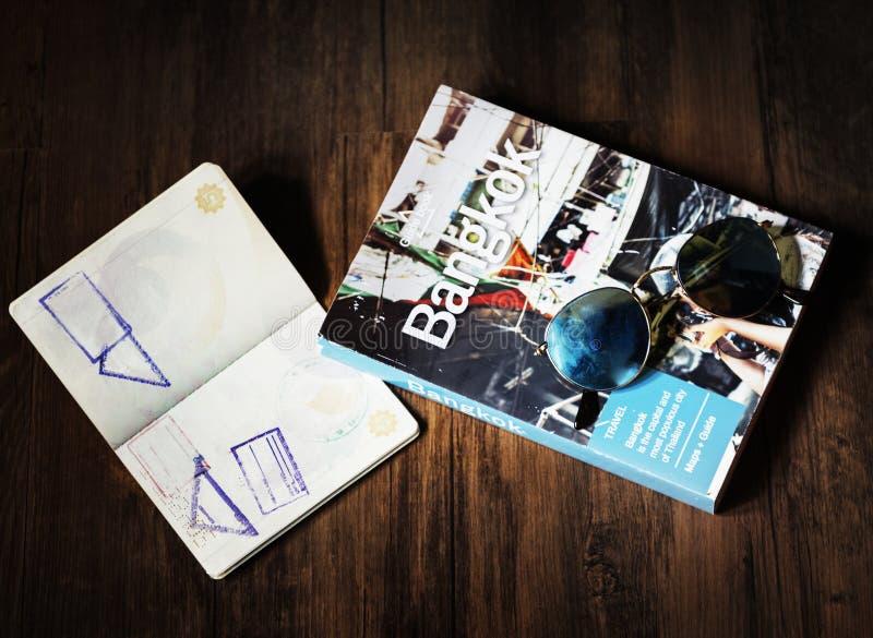Plan rapproché de passeport ouvert avec le guide de Bangkok Thaïlande sur la table en bois image libre de droits