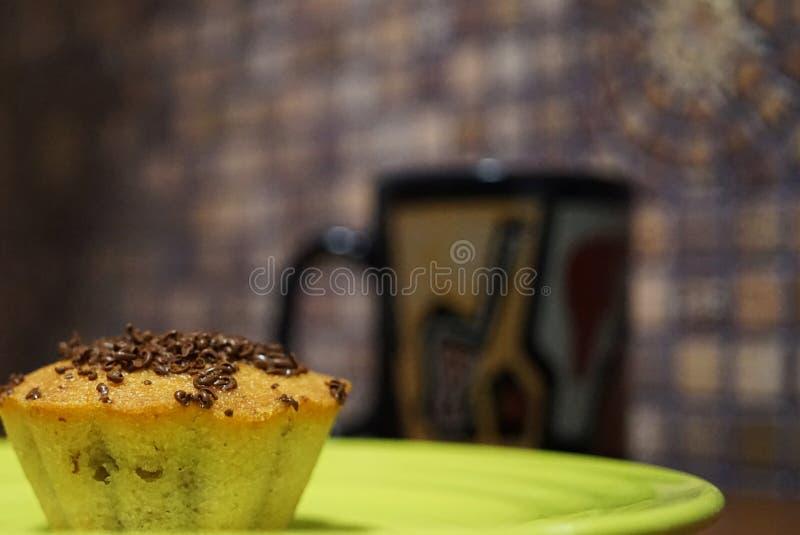 Plan rapproché de petit gâteau de vanille sur le fond d'une tasse noire avec le thé photographie stock libre de droits