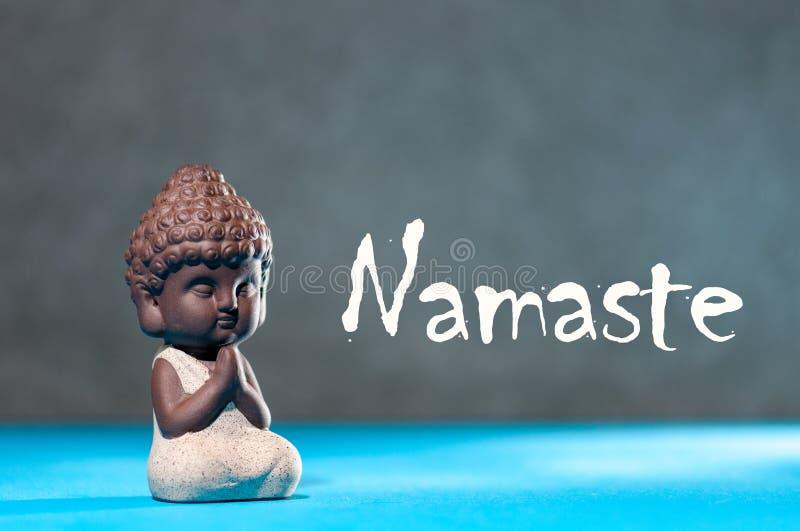 Plan rapproché de petit méditer de Bouddha, de foyer sur des bras dans le namaste de geste et de textes de Namaste - concept de y images stock
