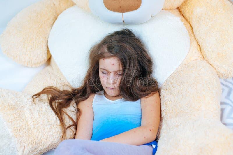 Plan rapproché de petite fille triste mignonne près de l'ours de nounours Virus de Varicella ou éruption de bulle de varicelle su photos libres de droits