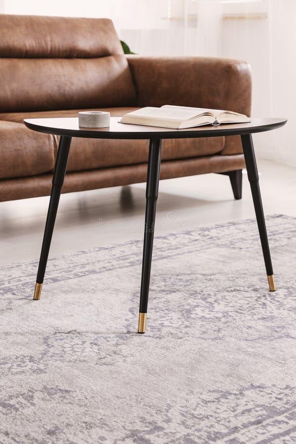 Plan rapproché de petite table avec la bougie et le livre, se tenant à côté du sofa en cuir de front dans le salon photographie stock