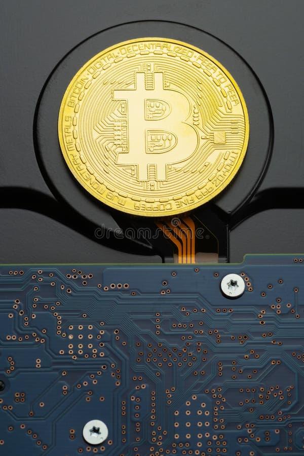 Plan rapproché de pièce de monnaie physique de criptocurrency de Bitcoin sur le lecteur de disque dur images stock