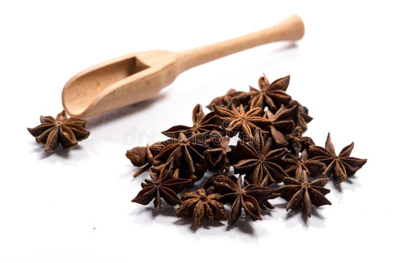 Plan rapproché de pile d'épice d'anis d'étoile dans une cuillère en bois sur le blanc photographie stock