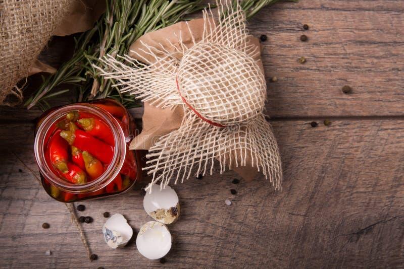 Plan rapproché de poivre de piment épicé rouge dans un pot en verre, coquilles des oeufs de caille et brindilles de romarin sur u photos libres de droits