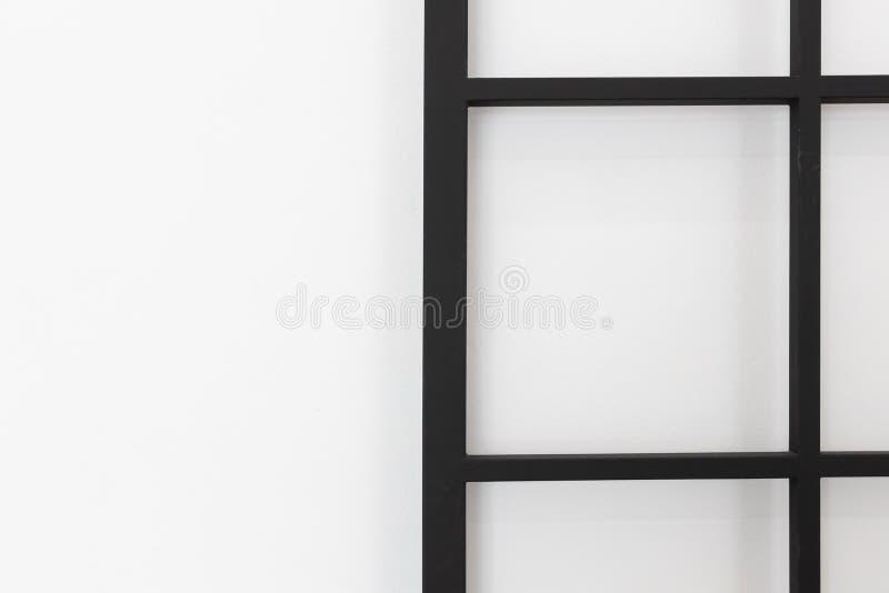 Plan rapproché de porte noire de gril de place en métal ou grille de glissement sur le fond blanc de mur en béton photos libres de droits