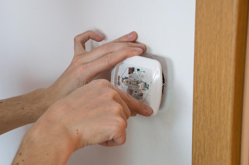 Plan rapproché de pour les mains électriques qui installant l'interrupteur de lampe électrique photographie stock libre de droits