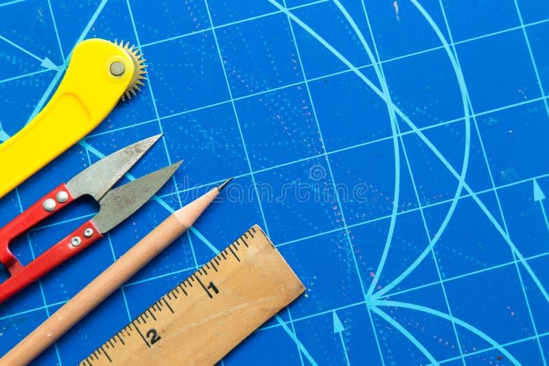Plan rapproché de règle, ciseaux, coupeur, crayon sur le tapis bleu de coupe photos libres de droits