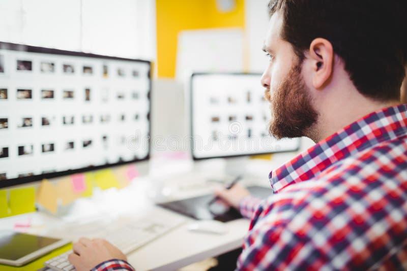 Plan rapproché de rédacteur se concentrant sur des photographies dans l'ordinateur au bureau créatif image libre de droits