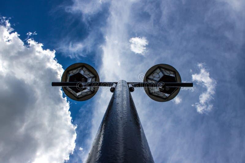 Plan rapproché de réverbère sur un haut poteau sur un fond de ciel bleu pur avec les nuages blancs photographie stock