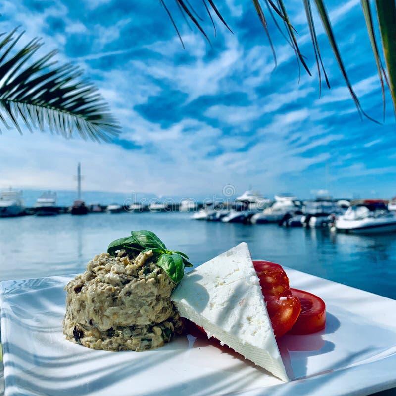 Plan rapproché de riz avec du fromage et la tomate près d'un dock de bateau un jour ensoleillé photographie stock libre de droits