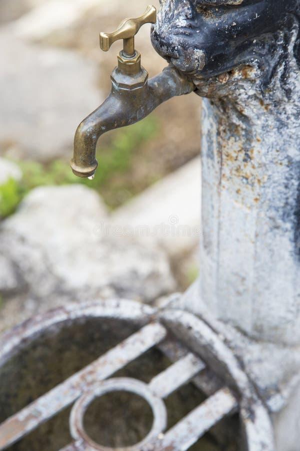 Plan rapproché de robinet de fer fermé, avec une goutte de l'eau photographie stock