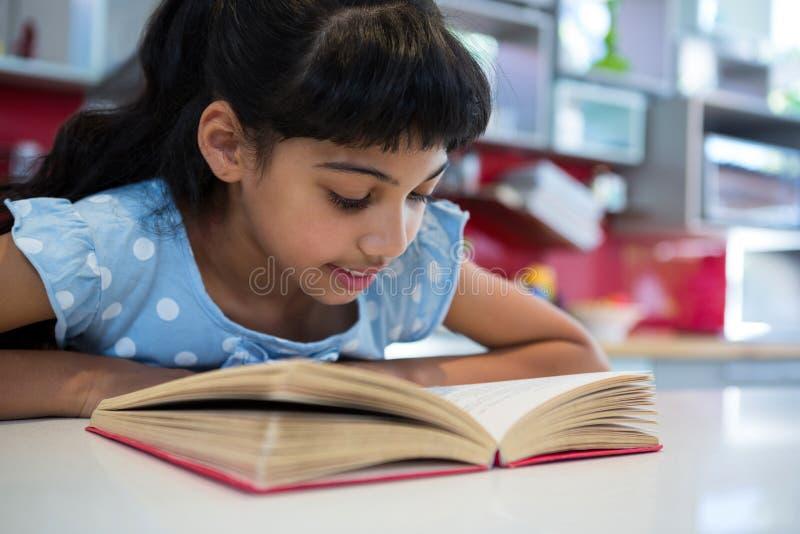 Plan rapproché de roman de lecture de fille dans la cuisine photos libres de droits