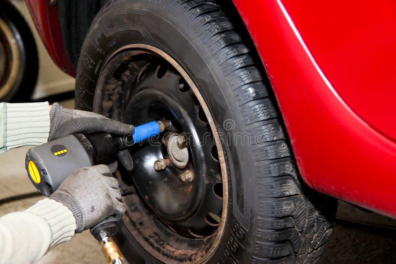 Plan rapproché de roue de changement sur le véhicule - avec pneumatique images libres de droits