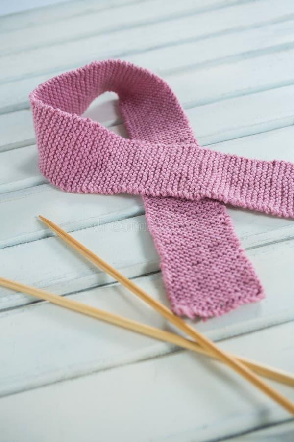 Plan rapproché de ruban de laine rose de conscience de cancer du sein par des aiguilles de crochet images stock