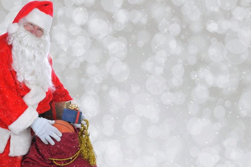 Plan rapproché de Santa Claus avec sa valise des jouets au-dessus d'un bokeh argenté photo stock