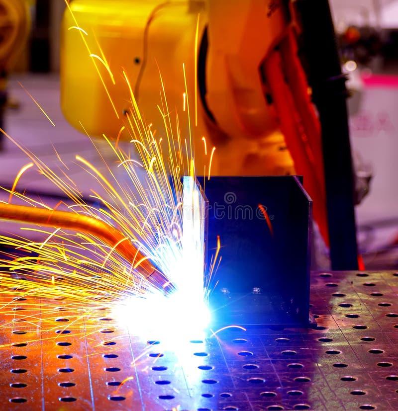 Plan rapproché de soudure de robot des flammes bleues et jaunes avec le jet dans l'usine profondeur de tache floue de champ photos stock